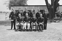 Ten naval officers in uniform sitting for a group portrait: four sitting on a bench, with the other six standing behind. A large, flat-roofed building, two trees, and some scattered people can be seen in the background