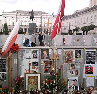 """Cross in front of the Presidential Palace, Warsaw - The cross, 10 September 2010, visible in the background. In front, the barricade wall decorated by the """"defenders"""" movement."""