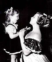 Woman kneeling down, in dress holding hand of young girl, both smiling