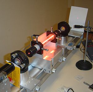 Laser - A helium–neon laser demonstration at the Kastler-Brossel Laboratory at Univ. Paris 6. The pink-orange glow running through the center of the tube is from the electric discharge which produces incoherent light, just as in a neon tube. This glowing plasma is excited and then acts as the gain medium through which the internal beam passes, as it is reflected between the two mirrors. Laser output through the front mirror can be seen to produce a tiny (about 1 mm in diameter) intense spot on the screen, to the right. Although it is a deep and pure red color, spots of laser light are so intense that cameras are typically overexposed and distort their color.