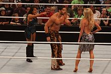 A brunette Caucasian woman and dark-haired Caucasian man in a wrestling ring, pointing and yelling at a blonde Caucasian woman with her back to the camera.
