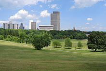 A rolling, grassy landscape with some trees beyond which some tall buildings can be seen under a blue sky with clouds. The tallest are light-colored modernist structures in the center of the image; smaller, older and darker buildings, including two church spires, rise above the treetops closer to the edges.