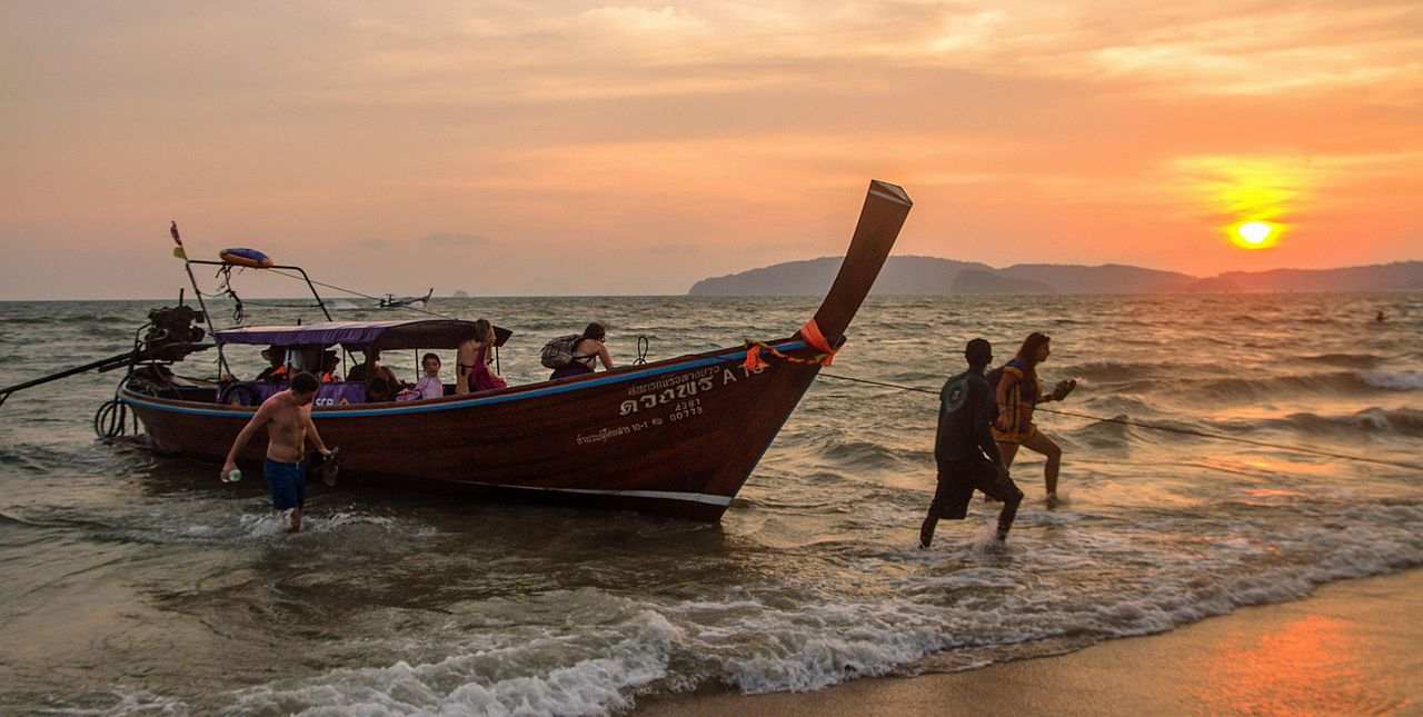 Long tail boat arrives to Ao Nang beach at sunset