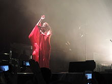 Lorde singing to a microphone onstage dressed in a red-colored outfit