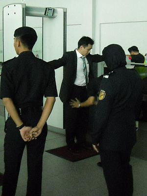 Auxiliary police - A Malaysia Airports auxiliary police officer examining a passenger to prevent dangerous goods from being brought onto an airplane Kota Kinabalu International Airport, Malaysia.