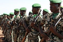 Soldiers lined up in a row, with green caps, carrying rifles