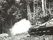 A tank fires into the jungle.