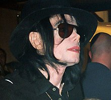 Jackson wearing a black hat and shirt, and dark sunglasses.