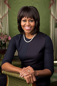 Michelle Obama facing forward, smiling, clad in black dress and single strand pearl necklace resting bare right forearm and both hands on a brocaded sofa armrest.