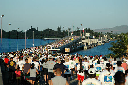 Hundreds of runners at the start line of a marathon at the O'ahu side of the Admiral Clarey bridge.