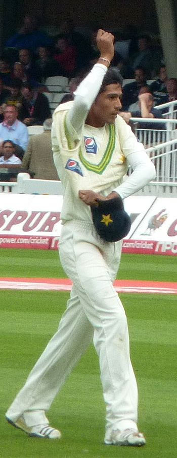 Mohammad Amir pulling on his jumper in the out...