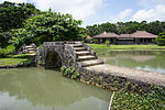 A pond crossed by a stone causeway with a bridge. There is a low wooden house beyond the pond.