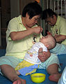 Nanny feeds infant at China Care Home.jpg