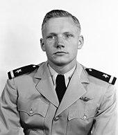 Een zwart-witafbeelding van een man met lichte huid in zijn vroege jaren '20.  Hij kijkt naar zijn rechterkant.  Hij heeft halfgekleurd haar aan de rechterkant.  Hij draagt een lichtgekleurd militair uniform met een adelaarsbadge op de linkerborst.  Zijn epauletten zijn donker en hebben een lichte balk en ster.  Hij heeft een wit overhemd en een donkere stropdas.