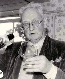 monochrome photograph of a man, wearing glasses and holding a brandy glass