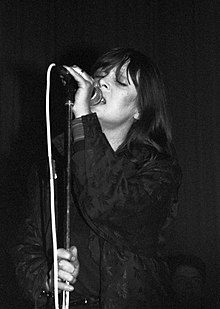 Nico singing into a microphone onstage