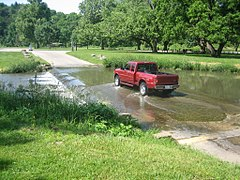 Vehicle crossing a modern ford over a creek