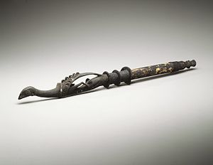 Papua New Guinea - Slaked lime holder, late 19th or early 20th century. The holder is decorated with wood carving of crocodile and bird. Details are emphasised with a white paint. The central portion, hollow to hold the slaked lime, is made of bamboo. The joints are covered with basketry work. The device is used in conjunction with chewing betel nut.