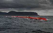 Un long tube rouge se trouve dans l'eau sous un ciel sombre couvert de nuages avec des collines noires au loin.