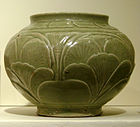 A green-grey bowl with a small bottom, a very wide center, and a top opening wider than the base but not as wide as the center. A pattern of out-dented large leaves covers the body of the bowl.