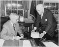 Photograph of President Truman receiving a birthday cake at his desk in the Oval Office from White House receptionist... - NARA - 200315.tif