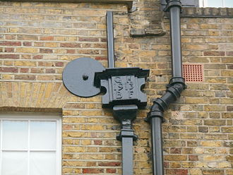 Benton Fletcher - This unusual rain hopper at 6 Buckingham Place SW1, is dated 1913 and bears the initials GHBF. George Henry Benton Fletcher acquired this house in 1913 and gave it to the National Trust in 1937.