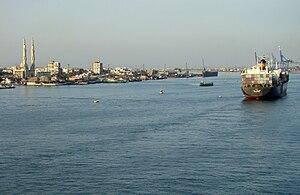 """Einfahrt in den Suezkanal bei Port Said, im Hintergrund Port Fouad mit seiner """"Großen Moschee"""