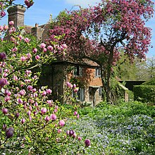 a view of a cottage in a garden full of flowers