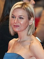 Profile of a female with short blonde hair wearing an azure dress.