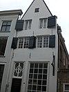 foto van Huis met gepleisterde tuitgevel, afgedekt door eensteens rollaag