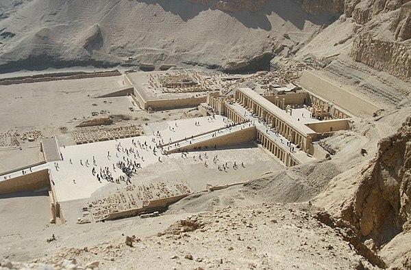 Kompleks w Deir el-Bahari. Na pierwszym planie świątynia Hatszepsut, w głębi świątynia Mentuhotepa II. Pomiędzy nimi znajdują się pozostałości świątyni Totmesa (Tutmozisa) III. Źródło: Wiki Commons, fot. Steve F-E-Cameron, lic. CC-BY-SA-3.0.