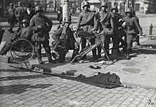 Seven soldiers of the German Army are stationed at a street corner in Helsinki after the surrender of the Red Guard headquarters Smolna. One of them is on his knee while two are relaxing against a railing or on a chair. MG 08, a heavy machine gun, rests in front of them.