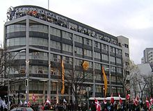 "A seven-story, modern building, predominantly grey and white, with a cross-like symbol and large letters spelling ""Scientology Kirche"" at the top. There is a crowd of people in front of the building, some of them with flags; the building itself is decorated with two yellow lengths of cloth and a large yellow cloth flower. Several dozen people are visible on the roof terrace."
