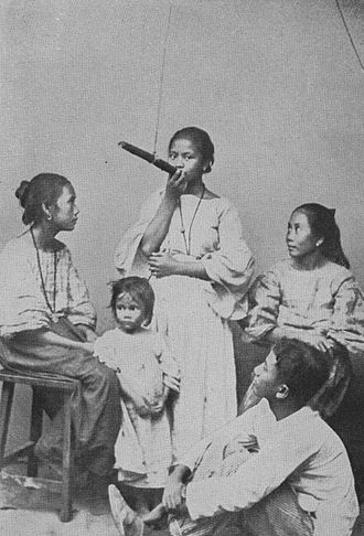 Photography in the Philippines - Smoking the Family Cigar, an early photograph of a Filipino family living in Northern Luzon. Photograph taken by James David Givens and published by Hicks-Judd Company in 1912.  This picture could have been taken earlier than 1912.