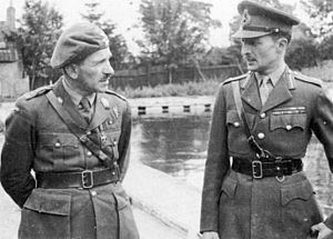 Two men in military uniforms with Sam Browne belts. The one on the left is wearing a beret, while the one on the right has a peaked cap.
