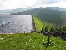 Daer Reservoir and dam with a blue footbridge extending out into the water and mown grass banks surrounding and a stone wall leading up to the dam