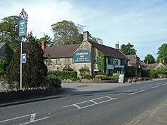 Building with pub sign saying the Sparkford Inn with car park and road in the foreground.