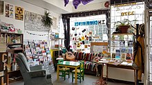 Sunlight shines through the window onto the hangout zone at Spartacus Books, which includes a couch, comfy chair, guitar, colourful magazine rack, posters, and patches. Date