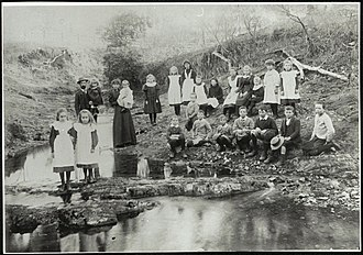 Gowrie, New South Wales - Pupils of Gowrie Public School in 1898. The teacher Mr. John Ward is nursing Eleena Ward, and his wife, Isobella (née Emblem) is nursing Laurie Ward. The two girls on the rock in the stream are Olive and Bernadine Ward whilst the boy standing and holding his hat is Norman Ward. The girls in the back row L. to R. are Ellie Frizzell, Eliza Whitten, Ellen Hough, Augusta McCulloch, May Moore, Ida Frizzell, Mildred Frizzell, Myrtle Moore and Maud Frizzell. The boys seated are L. to R. Wilfred Bailey, Vivian Bailey, Ernest Bailey, Percival Whitten, Jack White and Joseph McCulloch.