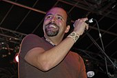 A man with a goatee and a t-shirt; he is smiling and his hand on a microphone stand