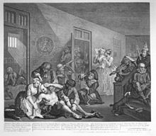 Engraving showing an insane asylum. In the foreground, an almost naked man being shackled and restrained by caretakers. On the stairs to the right, a violinist with sheet music on top of his head, and a man with a dunce cap on. In the background, two well-dressed women have come to view the inmates. Through doors in the background, we can see other mad inmates, all of them almost naked.