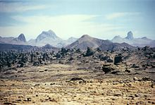 A hazy-looking yellow field of desert sand with rocks in the foreground and dark mountains and the blue sky in the background