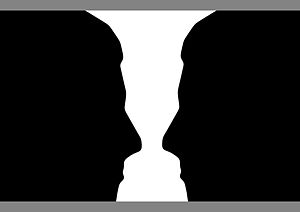 English: Two silhouette profiles or a white va...