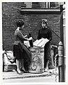 Two unidentified women place alleyway trash into a bin (13562040895).jpg