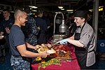 U.S. Navy Culinary Specialist 3rd Class Kendra Bellinger, right, serves roast beef to Yeoman Seaman Cesar Deguzman on the mess decks aboard the aircraft carrier USS Nimitz (CVN 68) Aug. 18, 2013, in the U.S. 5th 130818-N-LP801-002.jpg