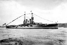 A large gray battleship sits in harbor