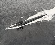 A surfaced submarine is seen from above and to port making high speed, with a long wake around and behind.