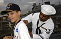 US Navy 030501-N-8787A-002 Postal Clerk 2nd Class Jamal Allison, assigned to the guided missile destroyer USS Cole (DDG 67) autographs a student's shirt during Fleet Week USA.jpg