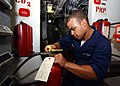 US Navy 040701-N-4374S-001 Fireman Alex Abreu performs a Planned Maintenance System (PMS) check on a CO2 fire extinguisher.jpg