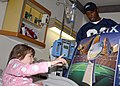 US Navy 050131-N-8544C-016 Child receives an autographed poster from Tampa Bay Buccaneer wide receiver Tim Brown during Super Bowl XXXIX festivities.jpg